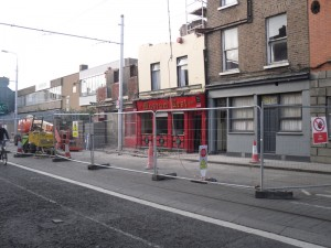 Photo of temporary fencing in front of damaged building